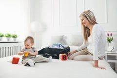 Déplacement avec des enfants La mère heureuse avec son emballage d'enfant vêtx pour des vacances Photos libres de droits