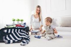 Déplacement avec des enfants La mère heureuse avec son emballage d'enfant vêtx pour des vacances Image stock
