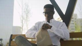 Déplacement de camionnette d' un jeune homme d' affaires africain américain se reposant et mangeant des croissants sur le banc d clips vidéos