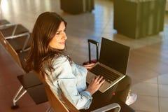 Déplacement de fille, se reposant avec l'ordinateur portable dans la salle d'attente d'aéroport Photographie stock