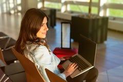 Déplacement de fille, se reposant avec l'ordinateur portable dans la salle d'attente d'aéroport Photo stock