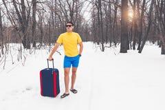 Déplacement de l'hiver à l'été Le jeune homme se tient dans des clothers d'été sur la neige et les rêves des vacances, mer, pays  image stock