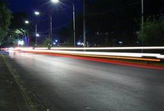 Déplacement de lumière de voiture brouillé sur la route de manière la nuit dans la ville Photos stock