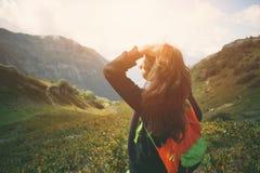 Déplacement de touristes de femme le long des prés de montagne Avec le petit sac à dos et les longs cheveux de tissage Soirée ave Image libre de droits