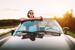 Déplacement par le couplr automobile dans le dgo d'amour en voiture de cabriolet dans le coucher du soleil Photos libres de droits