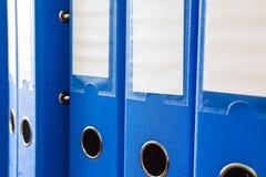 Dépliants de bureau d'isolement Rangée des dossiers bleus de bureau avec les labels vides sur le bureau Dossiers et documents org photos stock