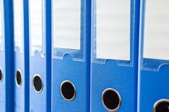 Dépliants de bureau d'isolement Rangée des dossiers bleus de bureau avec les labels vides sur le bureau Dossiers et documents org images stock