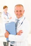 Dépliants mâles aînés de prise d'équipe de médecin Photo libre de droits