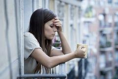 Dépression de souffrance de jeune belle femme triste semblant inquiétée et gaspillée sur le balcon à la maison Image stock