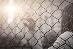 Déprimé, problème, aide et occasion La main désespérée d'augmenter de femmes sur la barrière de chaîne-lien demandent l'aide photos libres de droits