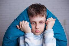 Dérangez le garçon soumis à une contrainte couvrant sa tête et oreilles bloquant le s photos stock
