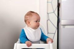 Dérangez peu d'enfant dans une chaise de bébé Images libres de droits