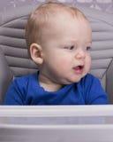 Dérangez peu d'enfant dans une chaise de bébé regardant loin Image libre de droits