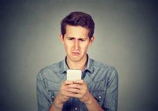 Dérangez a soumis à une contrainte l'homme jugeant le téléphone portable dégoûté avec le message reçu images stock