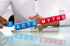 Déséquilibre d'apparence d'homme d'affaires entre les faits et les mythes photographie stock