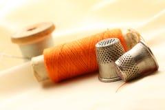 Dés, bobine et aiguille de couture Image stock