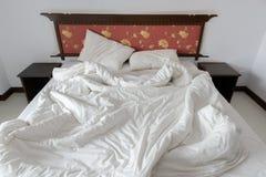 Désordonné/unmade le lit avec deux oreillers malpropres et un blanc a chiffonné la couverture dans un hôtel Photographie stock