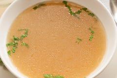 Désossez le bouillon fait à partir du poulet, servi dans une cuvette avec le persil Photographie stock libre de droits
