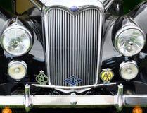 Détail avant d'une automobile noire de riley de vintage avec le radiateur et les insignes de butoir de phares Photographie stock