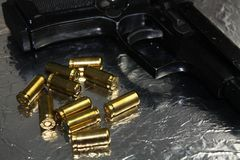 Détail d'arme à feu de pistolet avec les munitions d'or en laiton sur le bureau argenté brillant Photographie stock libre de droits