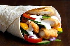Détail d'enveloppe panée de tortilla de poulet frit et de salade avec le whi image stock