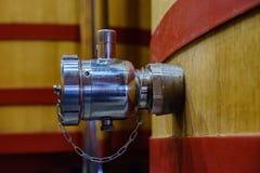 Détail d'un robinet en métal pour vider un grand baril où les raisins commencent à fermenter pour devenir vin photographie stock libre de droits