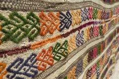 Détail d'un tapis décoré de laines Photographie stock