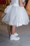 Détail d'une fille blanche de robe avec un arc et des coeurs blancs, des chaussettes blanches et des chaussures sur ses pieds Photos stock