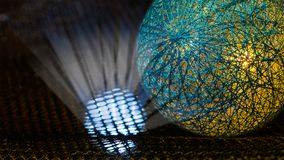 Détail d'une sphère couverte par le filet des fibres et des rayons légers de mystère dans l'espace noir photo stock