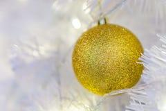 Détail de babiole d'or de Noël sur la branche blanche Photo libre de droits