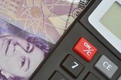 Détail de billet de banque et de calculatrice Photos stock
