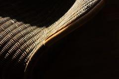 Détail de chaise de rotin avec la lumière du soleil et l'ombre Image stock