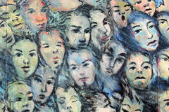 Détail de graffiti peint de visages sur le mur de Berlin Photos stock