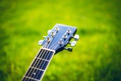 Détail de guitare acoustique sur une herbe Fond naturel avec les fleurs, l'herbe et le soleil Instrument musical Photos libres de droits