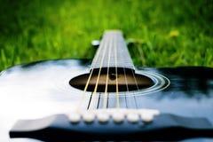 Détail de guitare acoustique sur une herbe Fond naturel avec les fleurs, l'herbe et le soleil Instrument musical Images stock