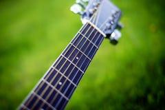 Détail de guitare acoustique sur une herbe Fond naturel avec les fleurs, l'herbe et le soleil Instrument musical Photo stock