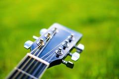 Détail de guitare acoustique sur une herbe Fond naturel avec les fleurs, l'herbe et le soleil Instrument musical Images libres de droits