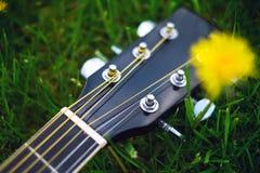 Détail de guitare acoustique sur une herbe Fond naturel avec les fleurs, l'herbe et le soleil Instrument musical Photographie stock