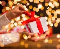 Détail de main de femme déroulant le cadeau de Noël Image libre de droits