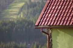 Détail de nouveau coin moderne de cottage de maison avec des murs de stuc décorés des pierres naturelles, du toit décalé rouge et images libres de droits