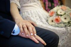 Détail de se tenir de bouquet et de mains de roses du ` s de jeune mariée Photographie stock