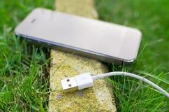 Détail de téléphone avec le câble sur l'herbe Photos stock