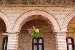 Détail des arcades rouges de brique de vintage, châssis de fenêtres et pot de fleur bruns de géranium accrochant Photos stock