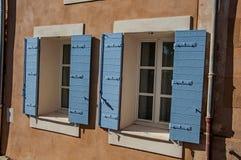 Détail des fenêtres avec les volets bleus au coucher du soleil dans le Comté de Roussillon Images stock