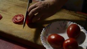 Détail des mains coupant une tomate banque de vidéos