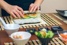 Détail des mains du roulement de chef de femme vers le haut des sushi japonais photos stock