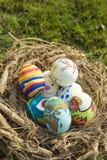 Détail des oeufs de pâques peints avec différentes formes, bandes dessinées et couleurs lumineuses placées dans un nid d'oiseau d photographie stock