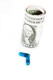 Détail des pilules bleues devant roulé vers le haut des dollars sur le fond blanc Images stock