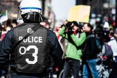 Détail du dos d'une police faisant face à des protestataires Image libre de droits