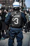 Détail du dos d'une police faisant face à des protestataires Photo stock